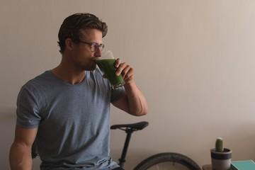 Man having a diet juice in living room