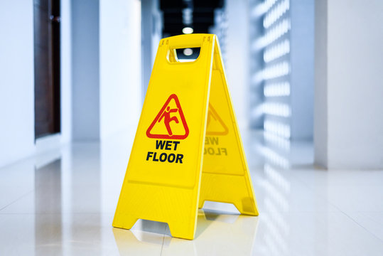 Sign showing warning of wet floor on wet floor