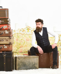 Man with beard and mustache packed luggage, white interior background. Luggage and relocation concept. Macho elegant on tired face sits, exhausted at end of packing, near pile of vintage suitcases.