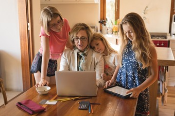 Mother and daughters using laptop and digital tablet