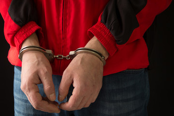 Criminal in handcuffs arrested for crimes.Close-up of a criminal hand in handcuffs