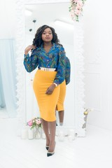 Attractive young African American woman in colorful ethnic clothes posing in the white studio with mirror on the background. Fashion portrait shot