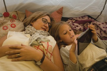 Mother and daughter relaxing in a tent at home