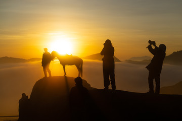 Silhouette of unidentified local people or Bromo Horseman pose for camera at the mountainside of Mount Bromo, Semeru, Tengger National Park, Indonesia.