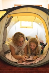 Mother and daughter using digital tablet in tent