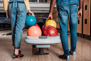 cropped shot of multiethnic couple with bowling balls standing in front of alleys at club