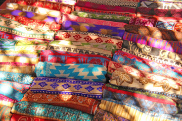 Warm colored Tibetan rugs are sold on the market in India. Bazaar India Tibet