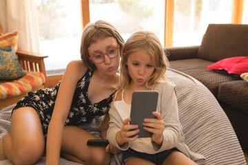 Siblings taking selfie on smartphone at home