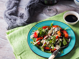 Salad with strawberries, arugula and parmesan drizzled with balsamic glaze