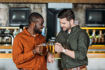 handsome young men with mugs of beer clinking at bar counter