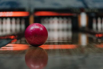 close-up shot of red bowling ball lying on alley under warm light
