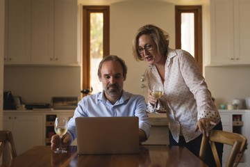 Couple having champagne while using laptop in kitchen