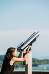 Young girl in black t-shirt is about to look through coin operated binoculars at the sea shore of Lake Constance.