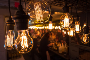 Group of unrecognizable young people during a party standing at the bar in an improvised warehouse environment that could be a school bulding with stylish lightbulbs decoration in the foreground