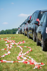 Cars parking in line in the green with red and white barrier tape at what might be a festival