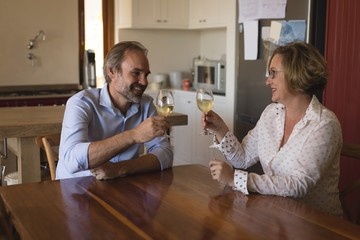 Couple enjoying champagne in kitchen at home
