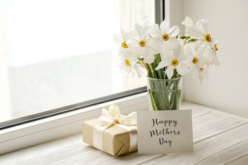 White yellow daffodil, narcissus flowers in glass vase on wooden windowsill, no window wiev. Happy mother's day text greeting card and craft paper prsent. Close up, copy space, still life, background.
