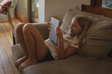 Girl using digital tablet in living room