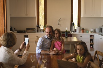Mother taking photo of father and daughter with mobile phone