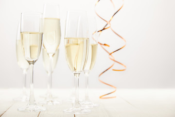 close up view of champagne glasses with ribbons on white wooden table, holiday concept