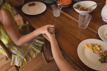 Sibling praying together before having lunch in kitchen at home