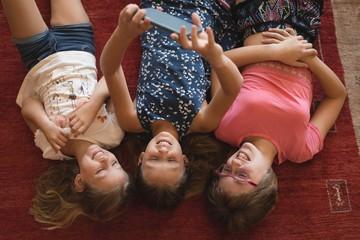 Siblings taking selfie with mobile phone in living room