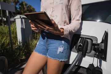 Woman using digital tablet while charging electric car at