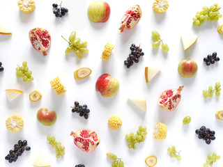 Concept of healthy food. Berries and fruit pattern. Slices of red apples,melon, pomegranate, black and green grapes on a white background.Composition of berries and fruits, top view. Food collage.