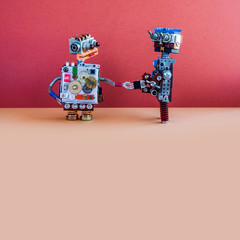 Creative design robotic toys, red wall brown floor background. Copy space