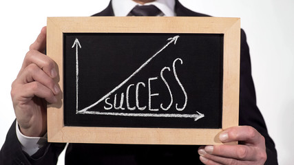 Success up arrow graphic drawn on blackboard in businessman hands, motivation