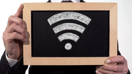 Wi-Fi zone sign drawn on blackboard in businessman hands, internet technology