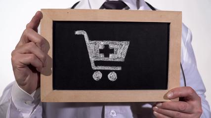 Drugstore cart drawn on blackboard in doctor hands, pharmaceutical business