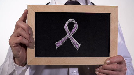 Breast cancer awareness pink ribbon symbol drawn on blackboard in doctor hands