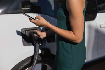 Woman using mobile phone while charging electric car at charging