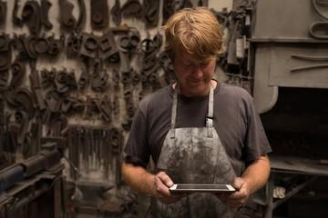 Blacksmith using digital tablet