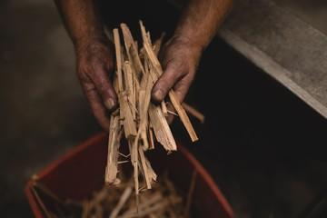 Blacksmith holding log sticks