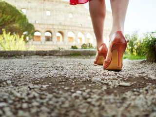 Crop shot of female feet in elegant high heels walking on alley with Colosseum on background.