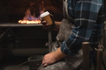 Blacksmith having coffee in workshop