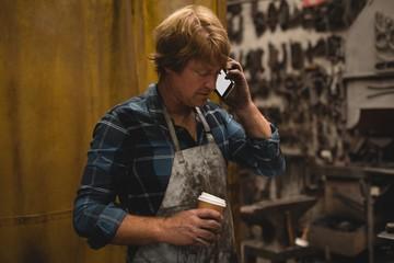 Blacksmith having coffee while talking on mobile phone