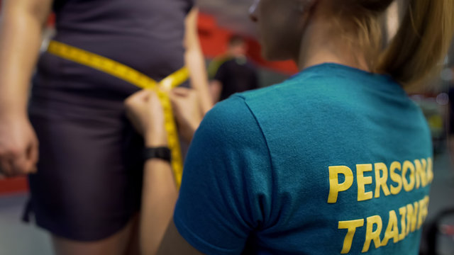 Personal trainer measuring waist of obese woman, checking results of exercising