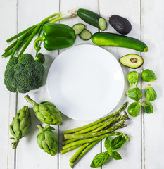 Plate surrounded by fresh green vegetables