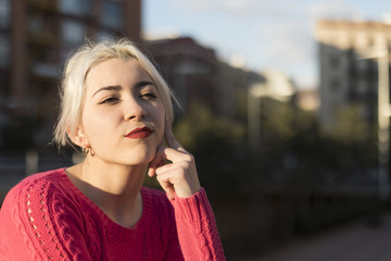Portrait of a young blonde woman gesturing in the street