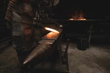 Blacksmith examining a hot metal rod