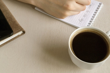 Top view of the goals list for the day, a Cup of coffee on a bright table.