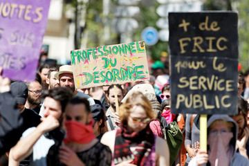 """Protesters hold a placard reading """"Disruption professionals"""" during a demonstration against the French government's reform plans in Lyon"""