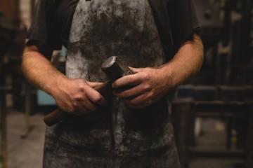 Blacksmith holding a hammer in workshop