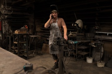 Blacksmith talking on mobile phone