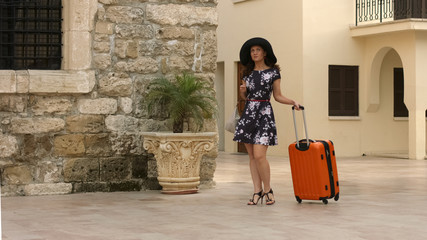 Woman with luggage looking for hotel, vacation in summer exotic city, tourism