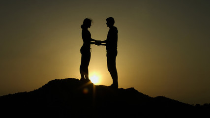 Two silhouettes holds hands on top of mountain against sunset, overcome together