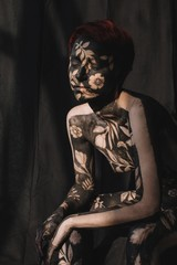 Portrait of a pensive woman in black and gold body paint